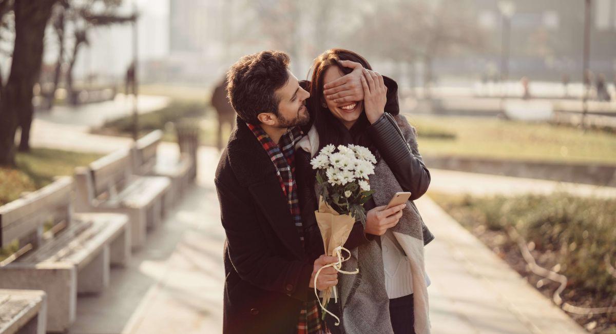 Mujer Hombre sorprendido con flores para el Día de San Valentín